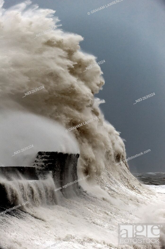 Stock Photo: Huge waves crash against the harbour wall at Porthcawl, Bridgend, Wales, UK.