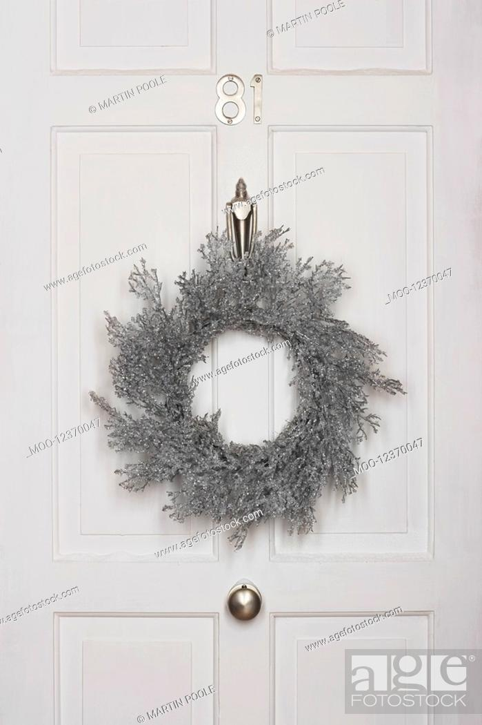 Stock Photo: Christmas wreath hanging on white door.