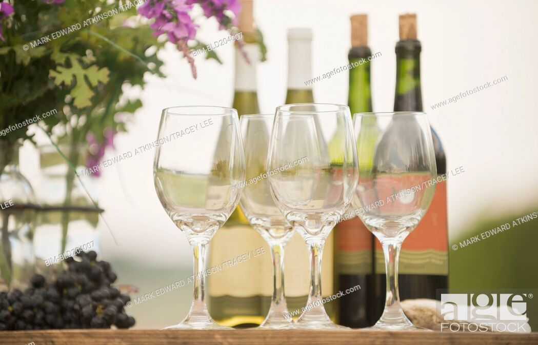Stock Photo: Wine bottle, grapes and glasses on table outdoors.