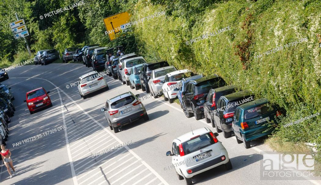 """Stock Photo: 24 July 2019, Schleswig-Holstein, Scharbeutz: Vehicles park in a bend in the road embankment. (To dpa-Korr """"""""bathing resorts in a dilemma."""