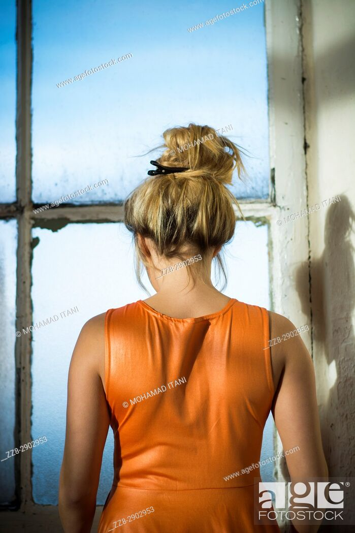 Stock Photo: Rear view of a blond woman hair up standing by the window.