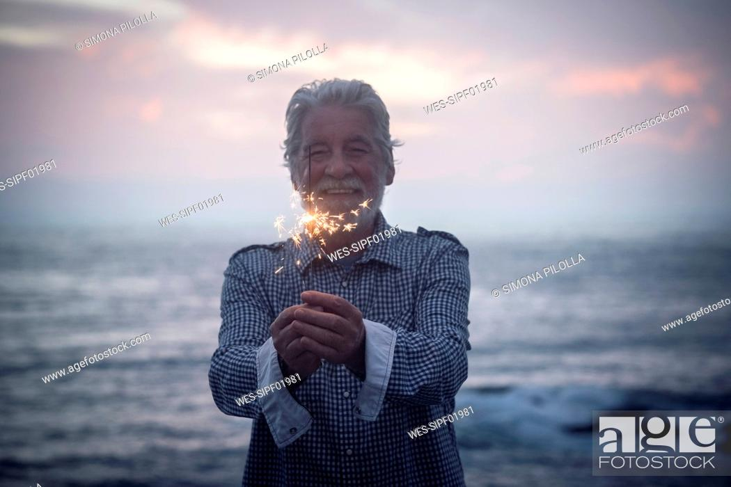 Imagen: Happy senior man standing in front of the sea by sunset holding sparkler.
