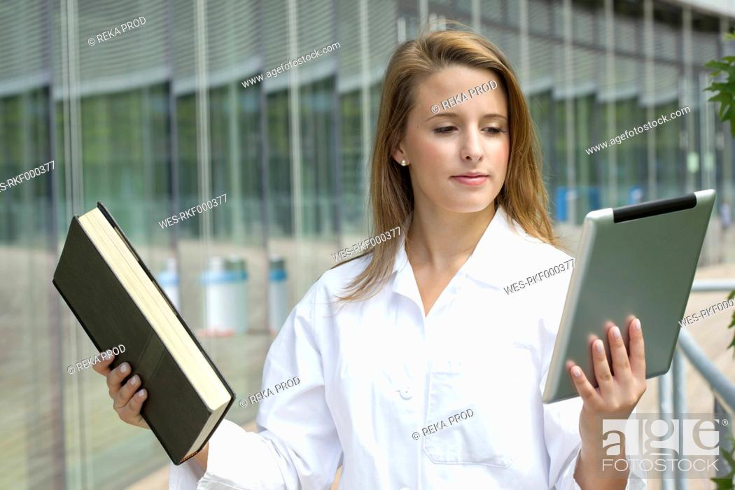 Stock Photo: Europe, Germany, North Rhine Westphalia, Duesseldorf, Medical student comparing book with digital tablet.