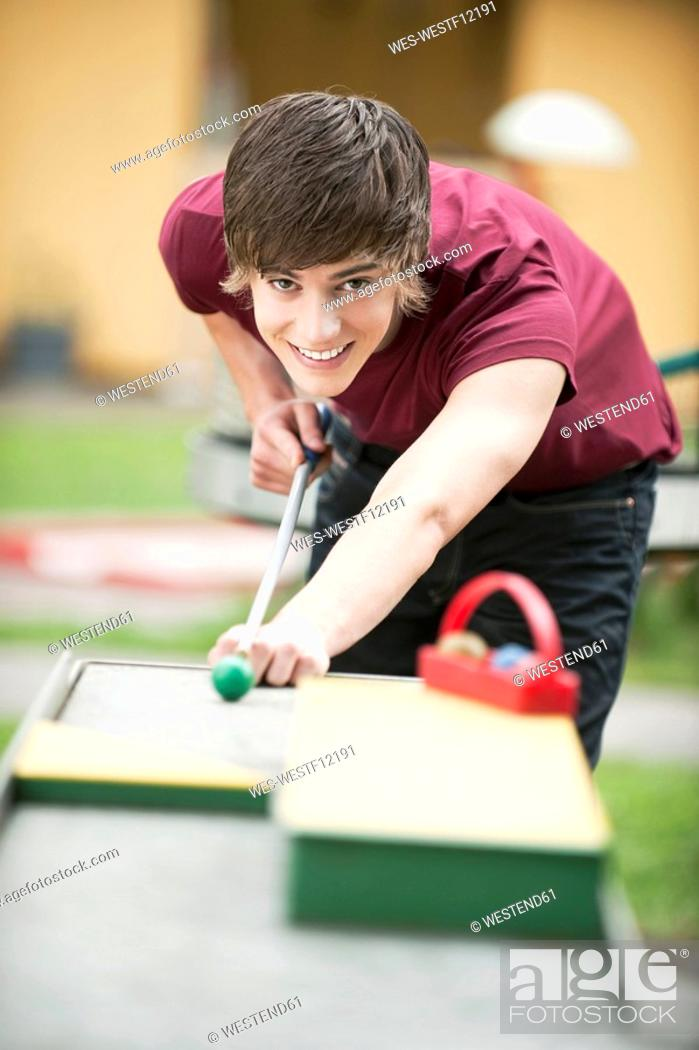 Stock Photo: Germany, Bavaria, Young man playing pool outside, portrait.