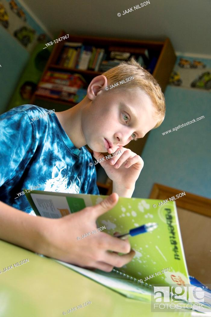Stock Photo: Serious Teenage Boy Sitting at Home Desk and Learning.