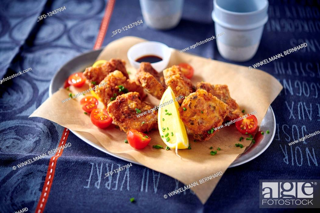 Stock Photo: Breaded, fried hake with cherry tomatoes on baking paper.