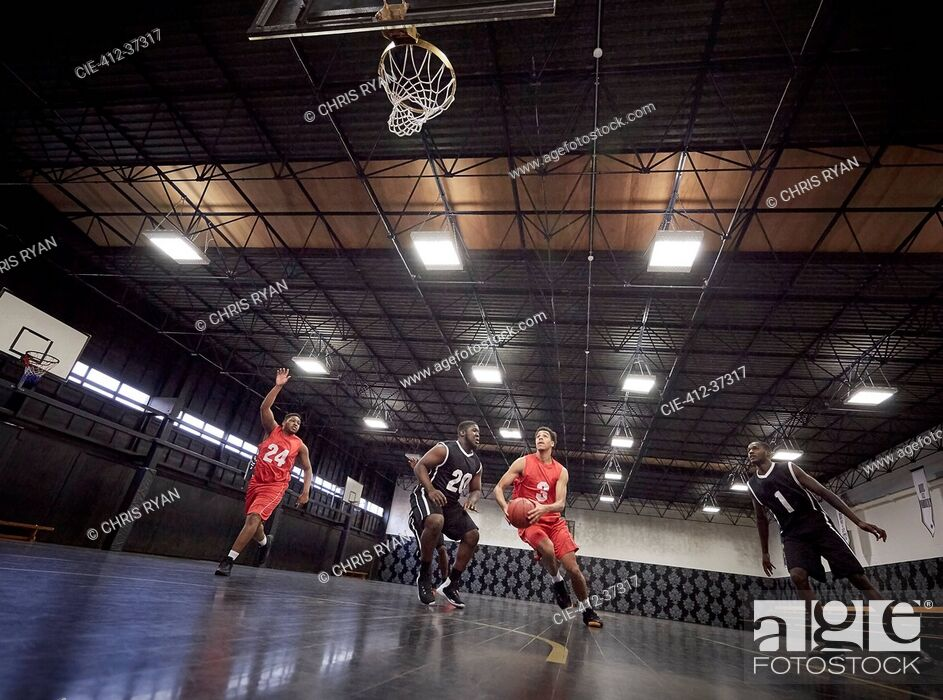 Stock Photo: Young male basketball players playing basketball on court in gym.