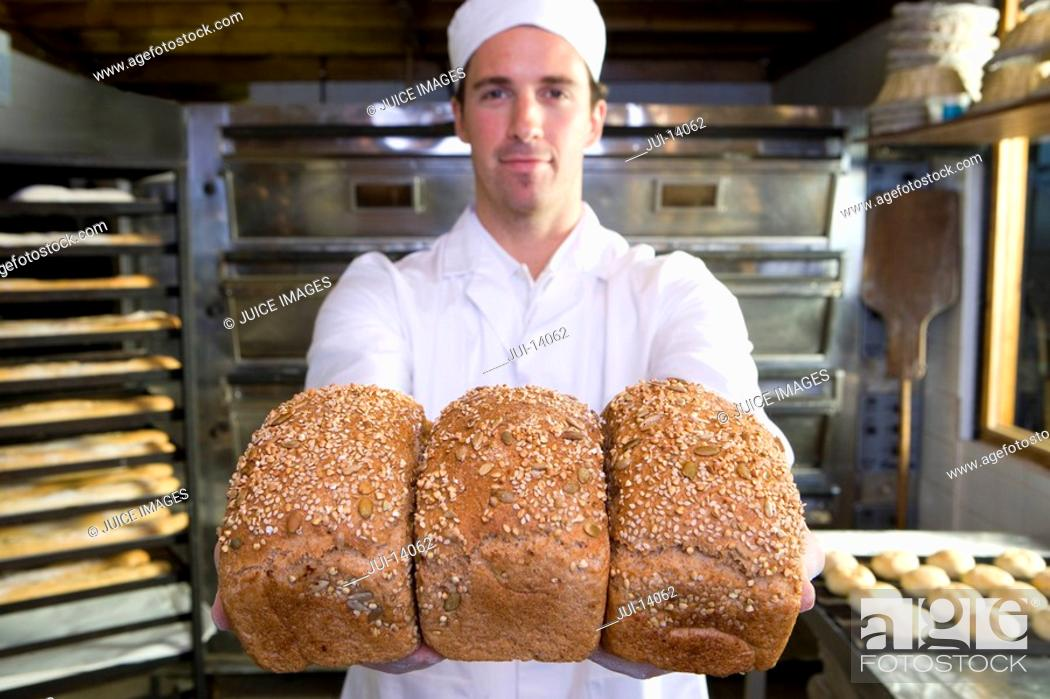 Stock Photo: Baker with loaves of bread, portrait.