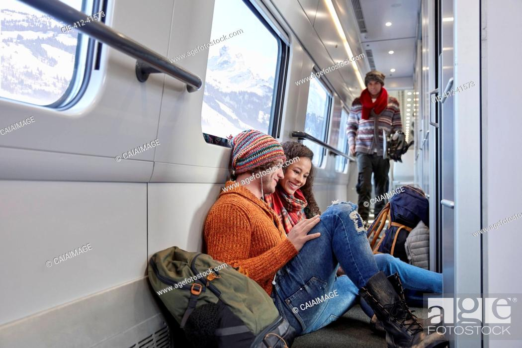 Stock Photo: Young couple backpacking, riding passenger train.