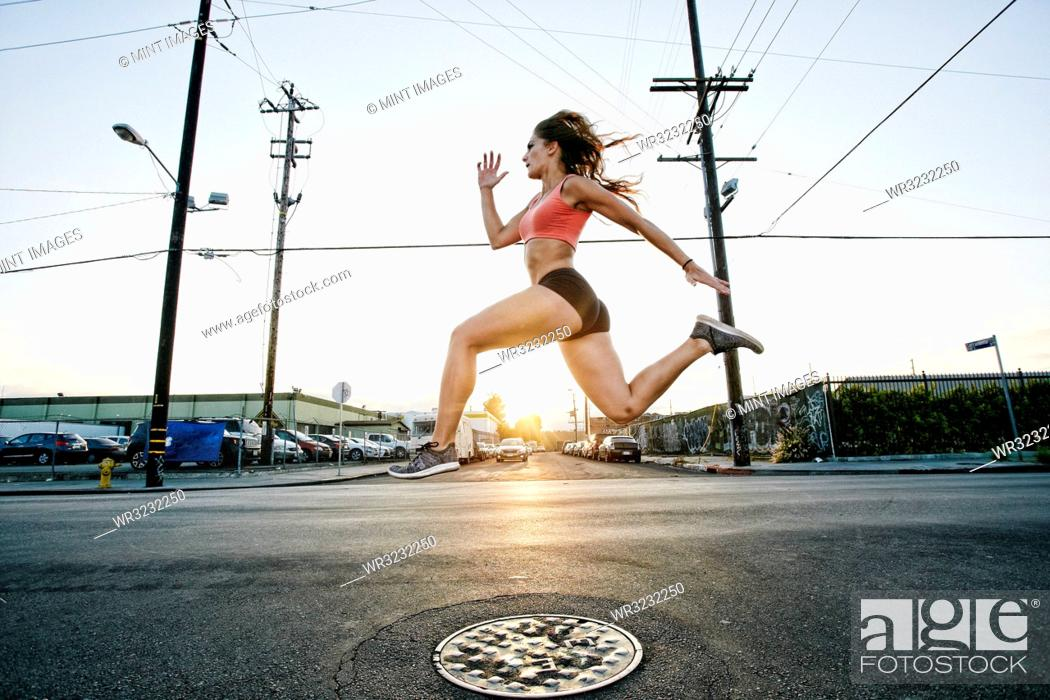 Stock Photo: Female athlete running along street at dusk.