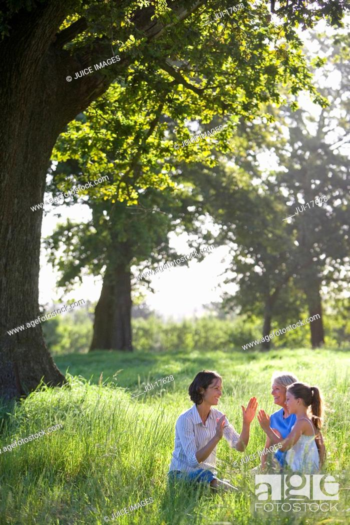 Stock Photo: Mothers and daughters playing in field.
