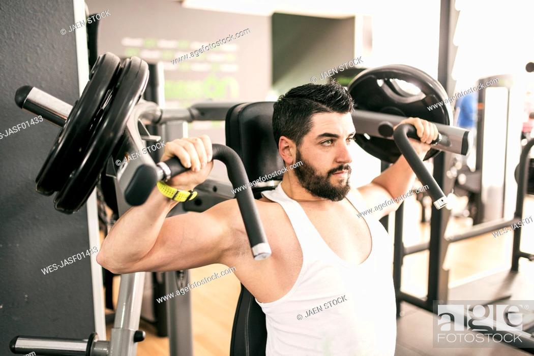 Stock Photo: Man exercising with shoulder machine in gym.