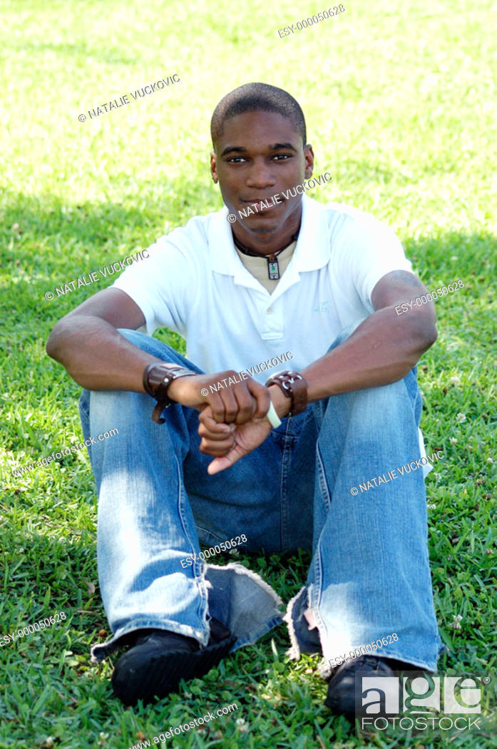 Stock Photo: Young African-American man sitting on grass.