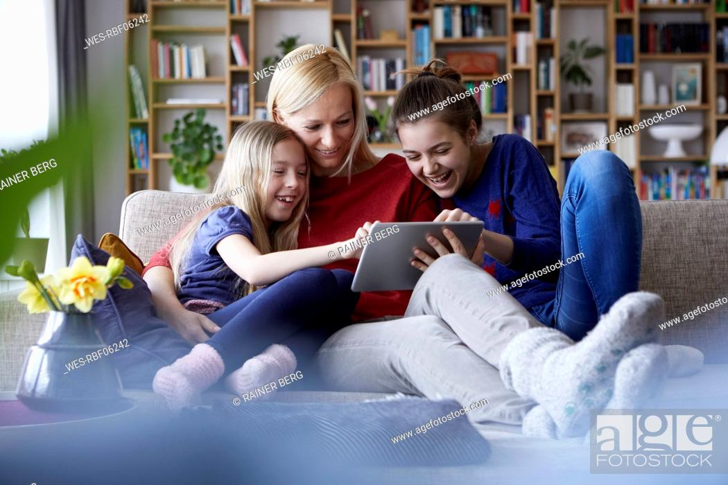 Stock Photo: Mother and her daughters sitting on couch, having fun using digital laptop.