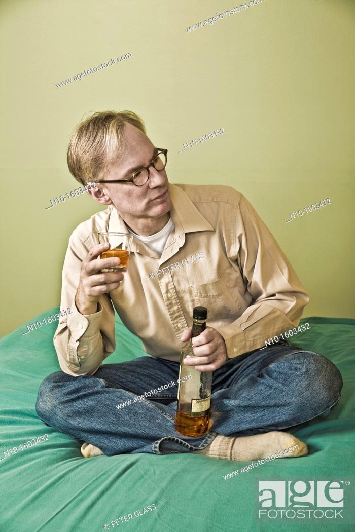 Stock Photo: Middle-age man holding a bottle and a glass of liquor.