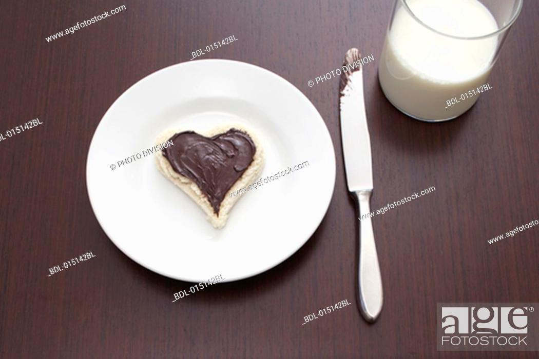 Stock Photo: still life of sandwich with spread cut out in shape of heart on plate and glass of milk.