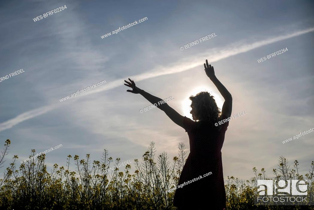Stock Photo: Silhouette woman with arms raised standing amidst oilseed rapes at sunset.