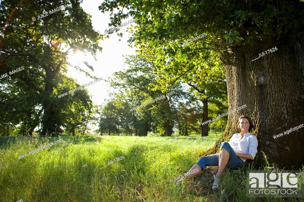 Stock Photo: Woman sitting by tree.