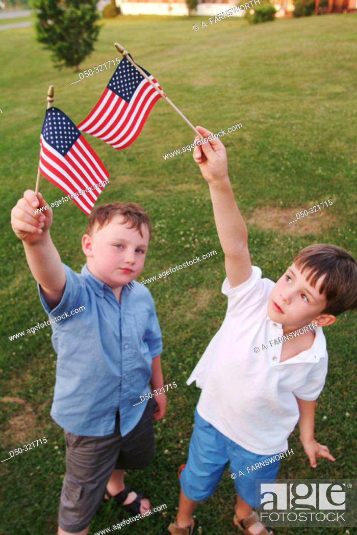 Stock Photo: Two six year olds waving the US flag. Swan Lake, New York, USA.