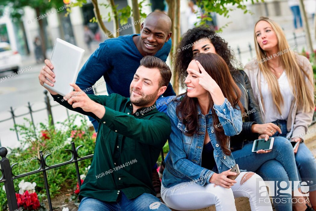 Stock Photo: Multi-ethnic group of young people taking selfie photograph together outdoors. Beautiful funny women and men wearing casual clothes in urban background.