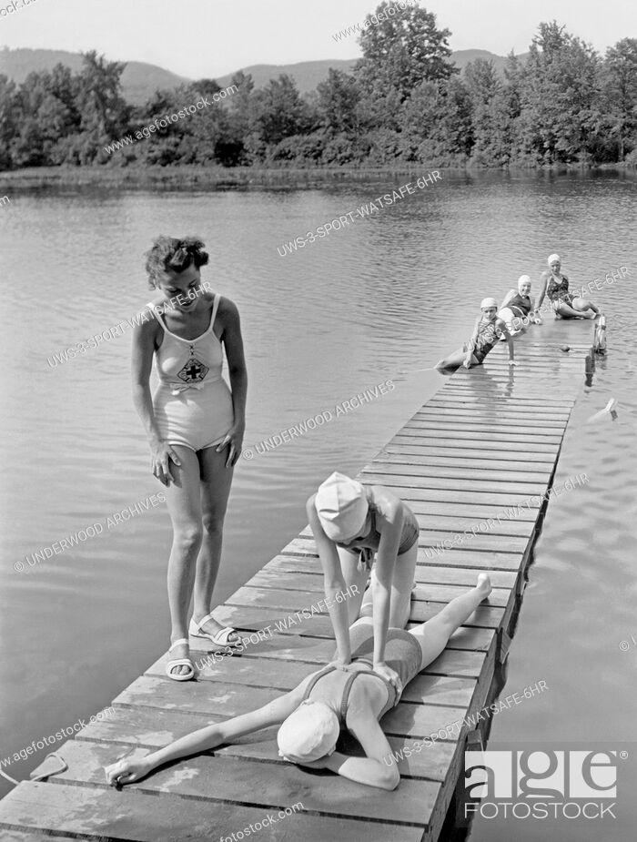 Stock Photo: Hadley, Massachusetts: c. 1928 A Red Cross water safety instructor teaches artificial respiration at the Girl Scout's Camp Lewis Perkins.
