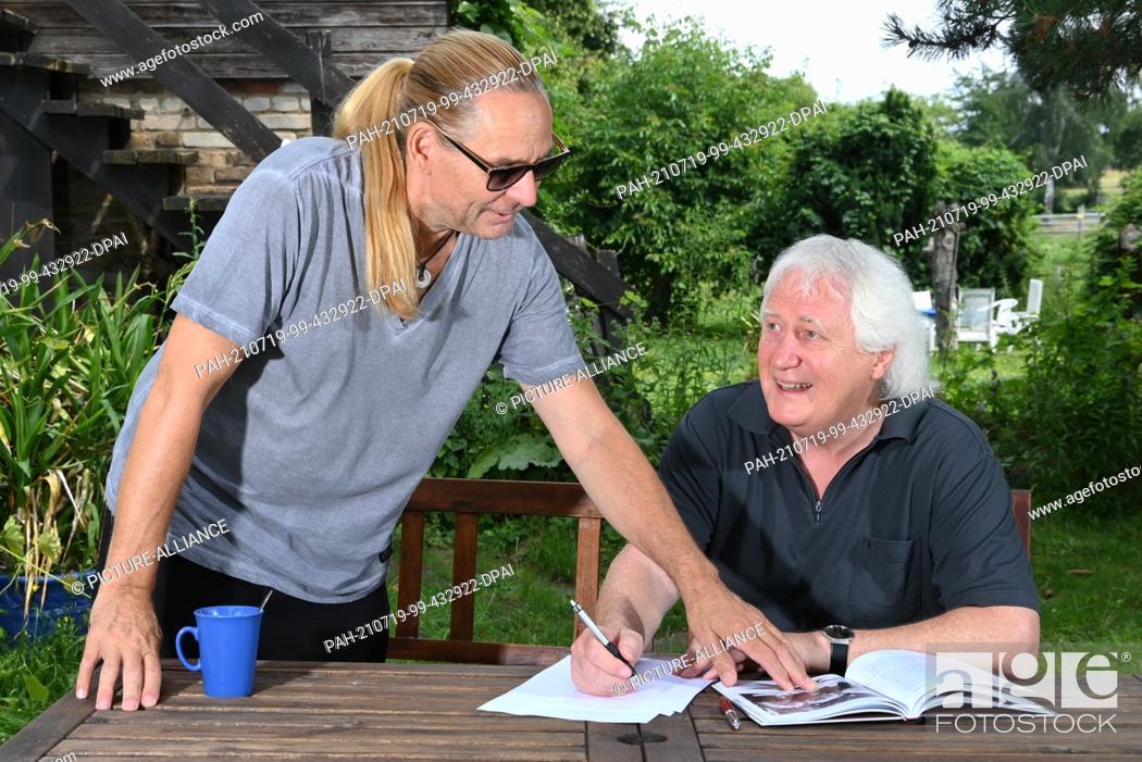 """Stock Photo: 16 July 2021, Brandenburg, Hoppegarten: Silly guitarist Uwe Hassbecker (l) and music expert Wolfgang Martin discuss the new book """"""""Paradiesvögel fängt man nicht."""