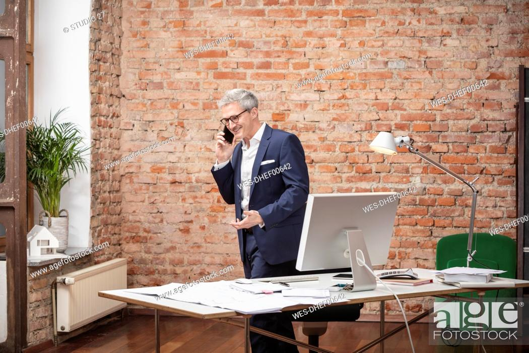 Stock Photo: Smiling male professional talking on mobile phone while working in office.