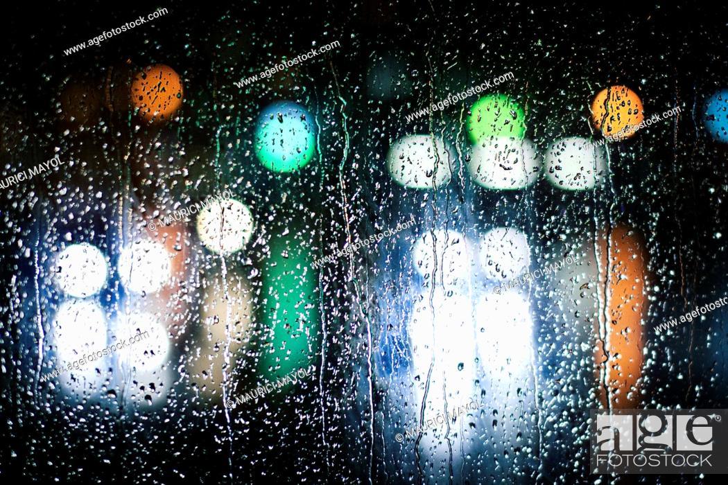Stock Photo: luces desenfocadas en un vidrio lleno de gotas de agua.