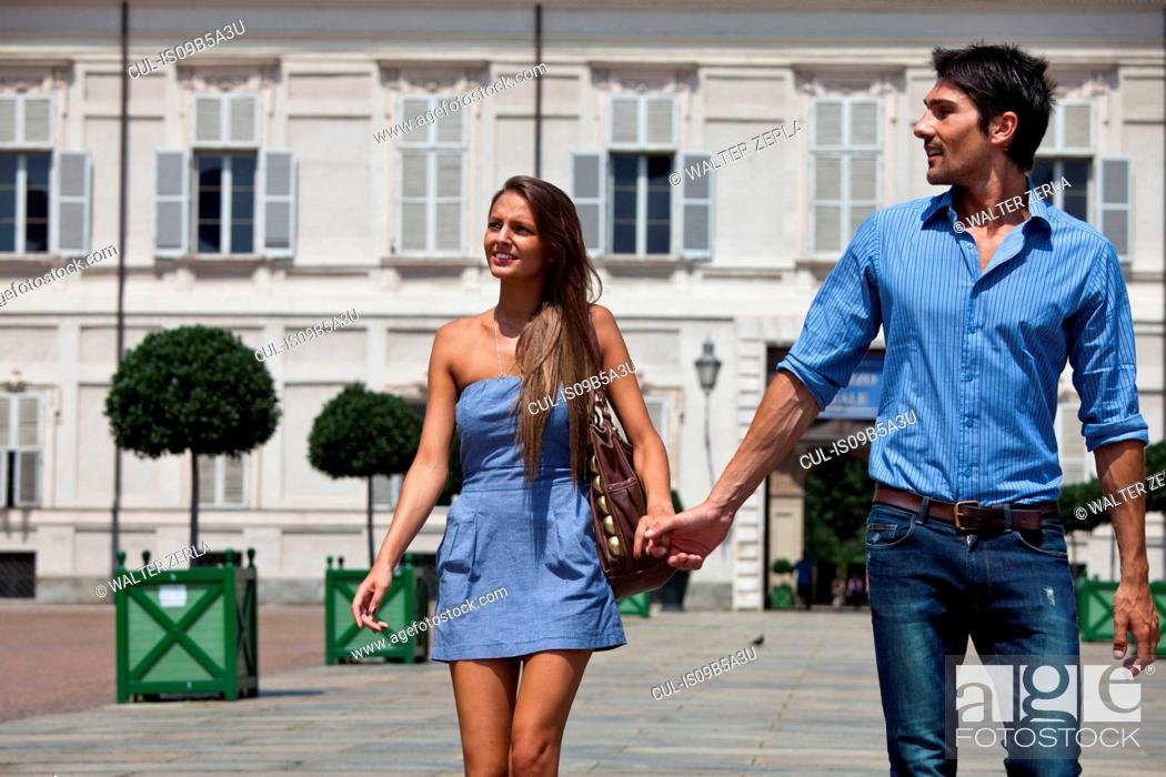 Stock Photo: Young couple walking outdoors, hand in hand, Turin, Piedmont, Italy.