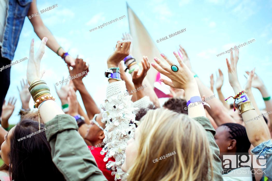 Photo de stock: Fans reaching to shake hands with performer at music festival.