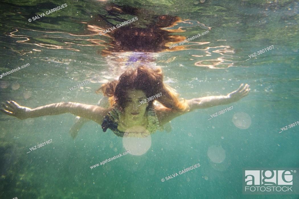 Stock Photo: A woman in a long dress dances and dives submerged under the sea, Javea, Alicante, Valencia, Spain.