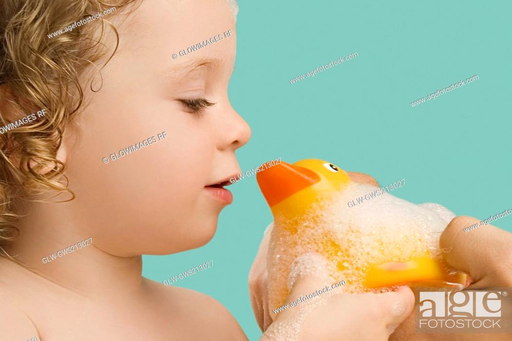 Stock Photo: Close-up of a girl holding a rubber duck and smiling.