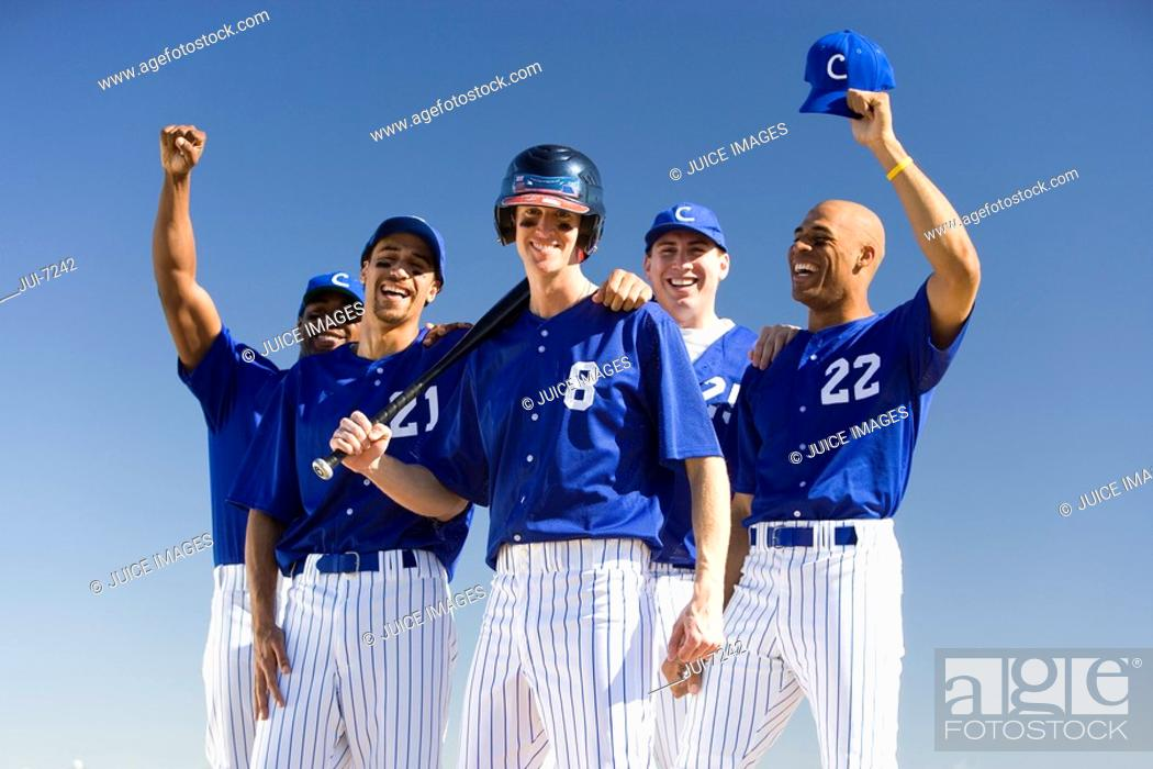 Stock Photo: Baseball team, in blue uniforms, celebrating victory post match, arms up, smiling, front view, portrait.