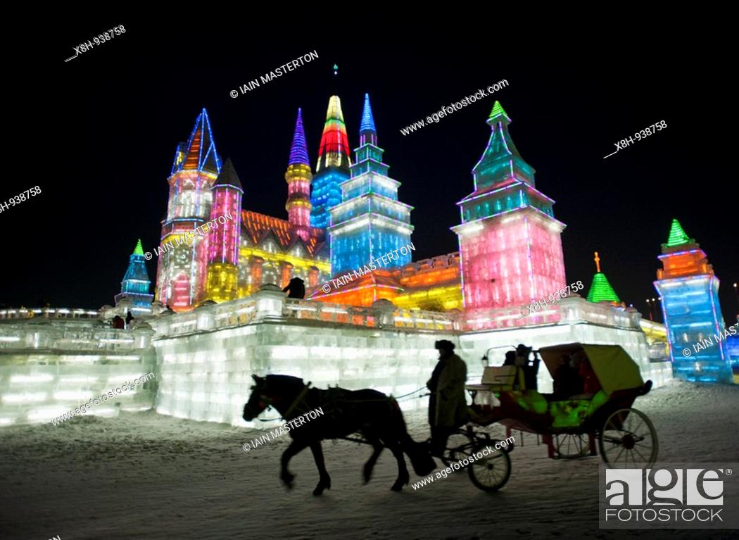 Stock Photo: Horse and carriage with large illuminated building sculpture at night at the annual Harbin Ice Lantern festival in 2009.