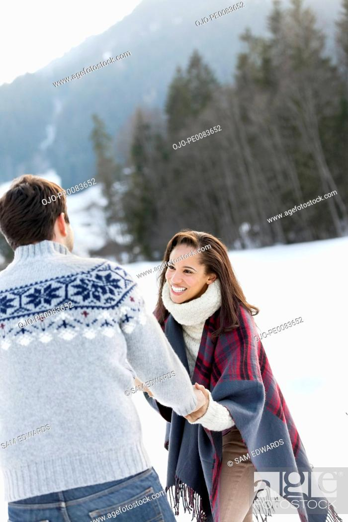 Stock Photo: Smiling couple holding hands in snowy field.