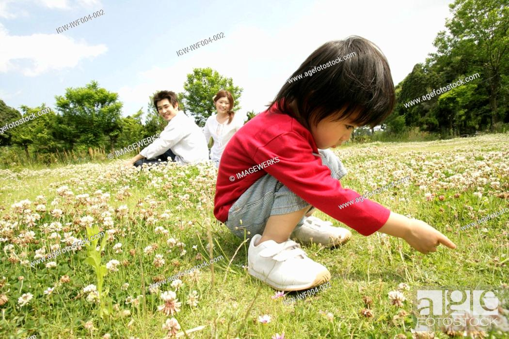 Stock Photo: A small boy stares at the grass in the garden as his parents looks on.