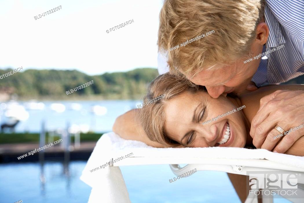 Stock Photo: Couple embracing on lounge chair.