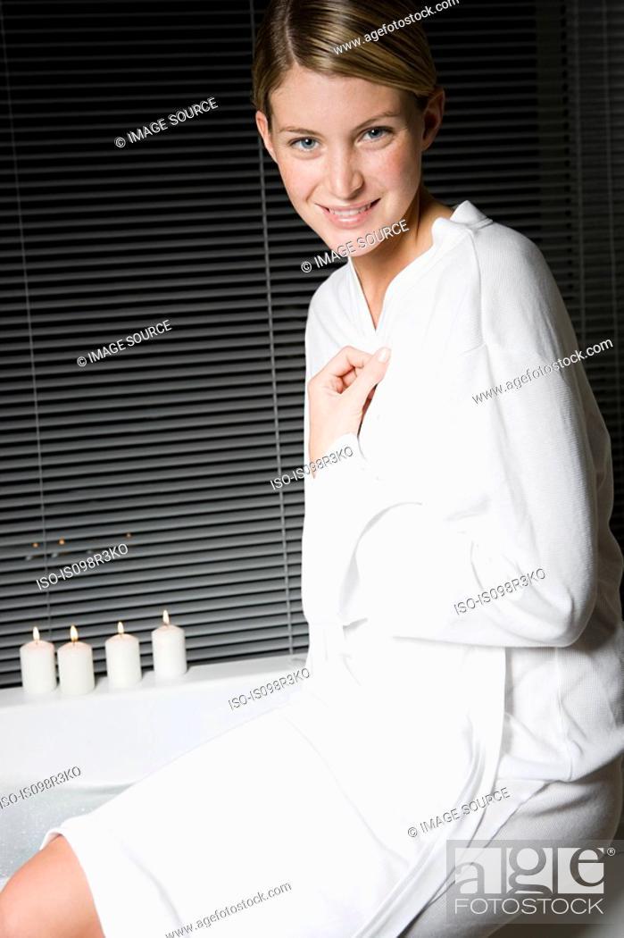 Stock Photo: Portrait of young woman in bathrobe sitting on bathtub.