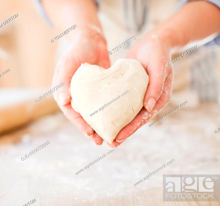 Stock Photo: Close up of woman holding heart-shape dough.