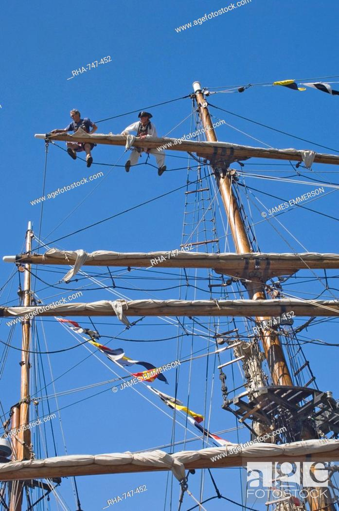 Stock Photo: Detail of main mast of tall ship with two seamen on top yard securing sail, Whitehaven, Cumbria, England, United Kingdom, Europe.