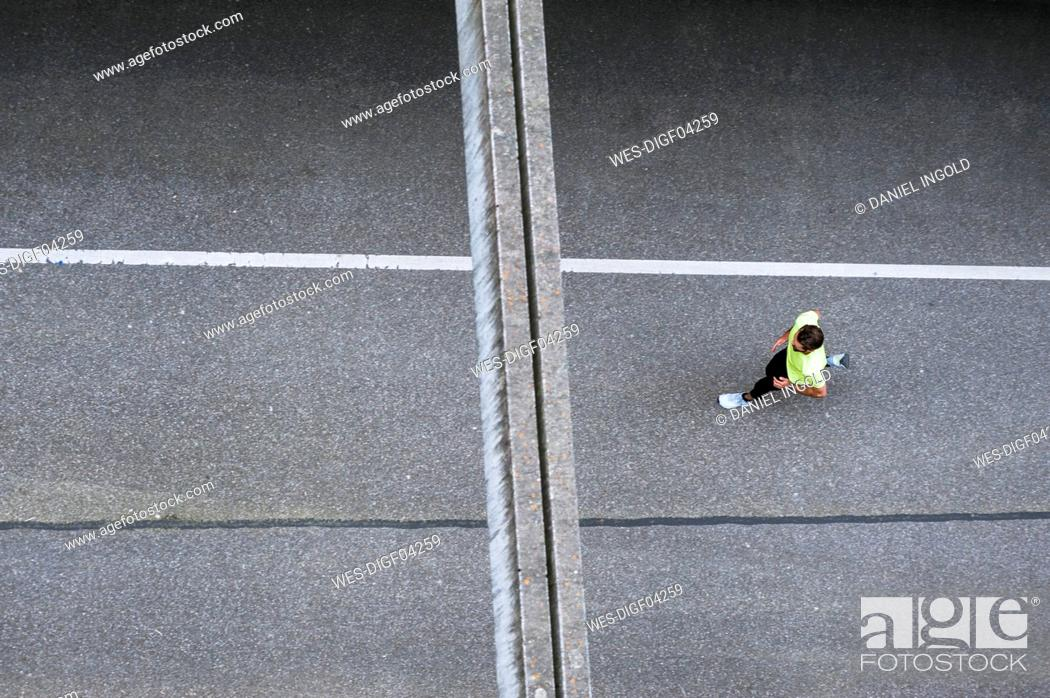 Stock Photo: Top view of man running on a street.
