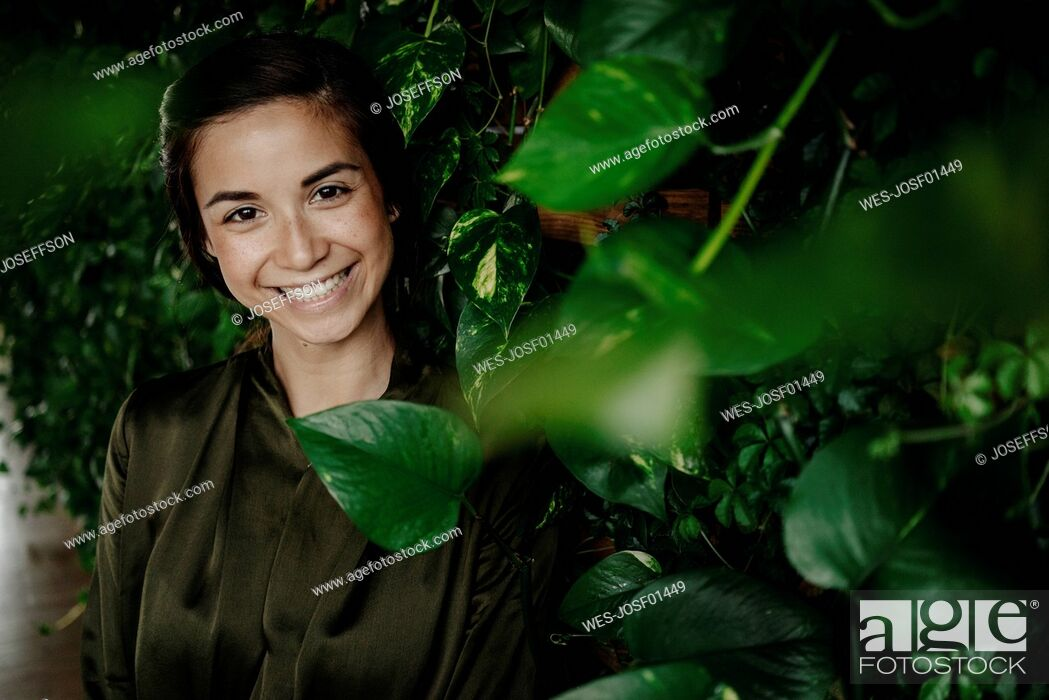 Stock Photo: Portait of smiling young woman at wall with climbing plants.