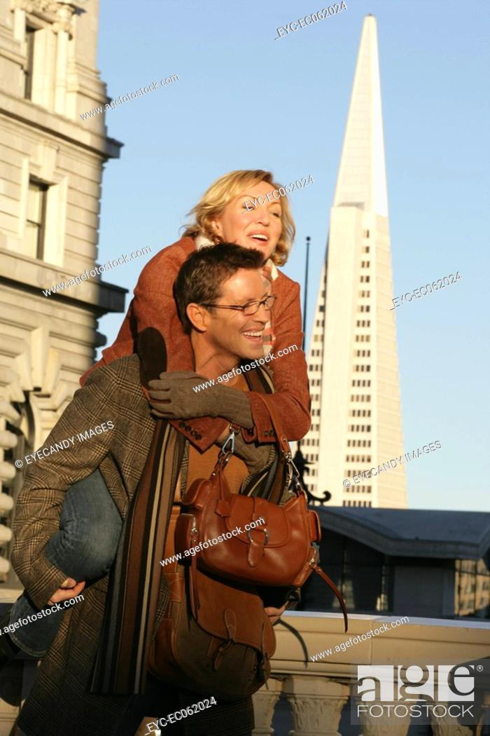 Stock Photo: Man giving woman a piggy back ride.