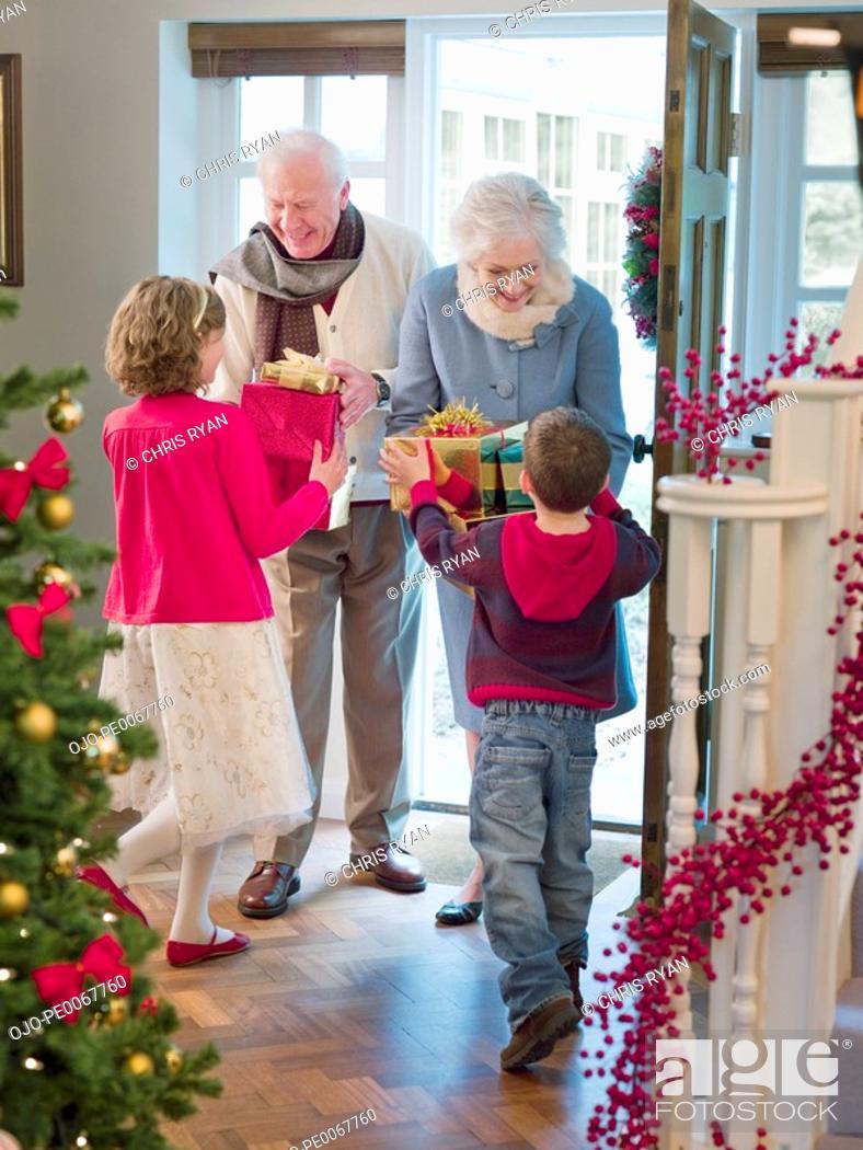 Stock Photo: Grandparents giving grandchildren Christmas gifts in doorway.
