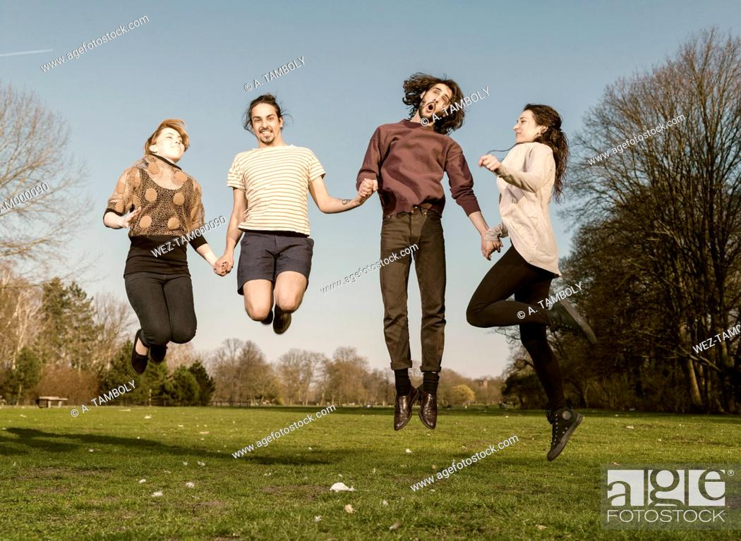 Imagen: Four friends on a meadow jumping together in the air.