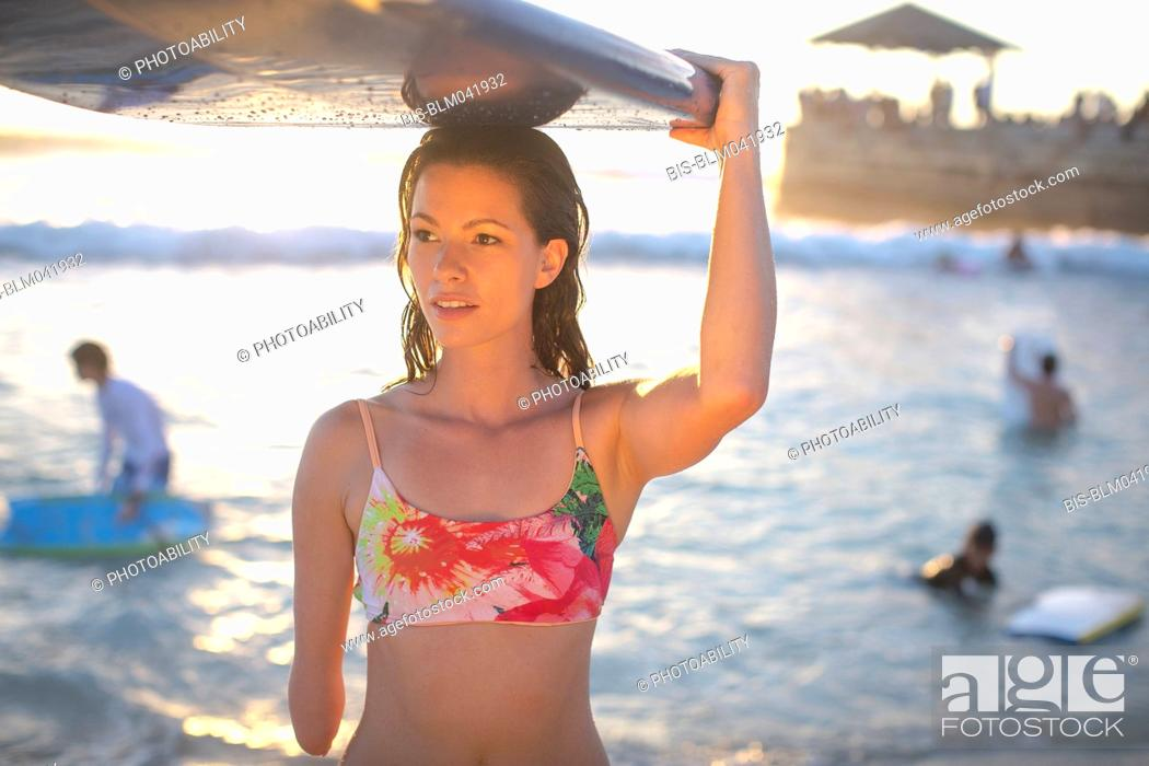 Imagen: Mixed race amputee carrying surfboard on beach.