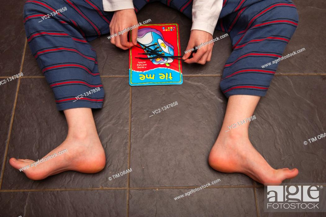 Stock Photo: A boy practises tying shoelaces on a learning card by orchard toys in the Uk.
