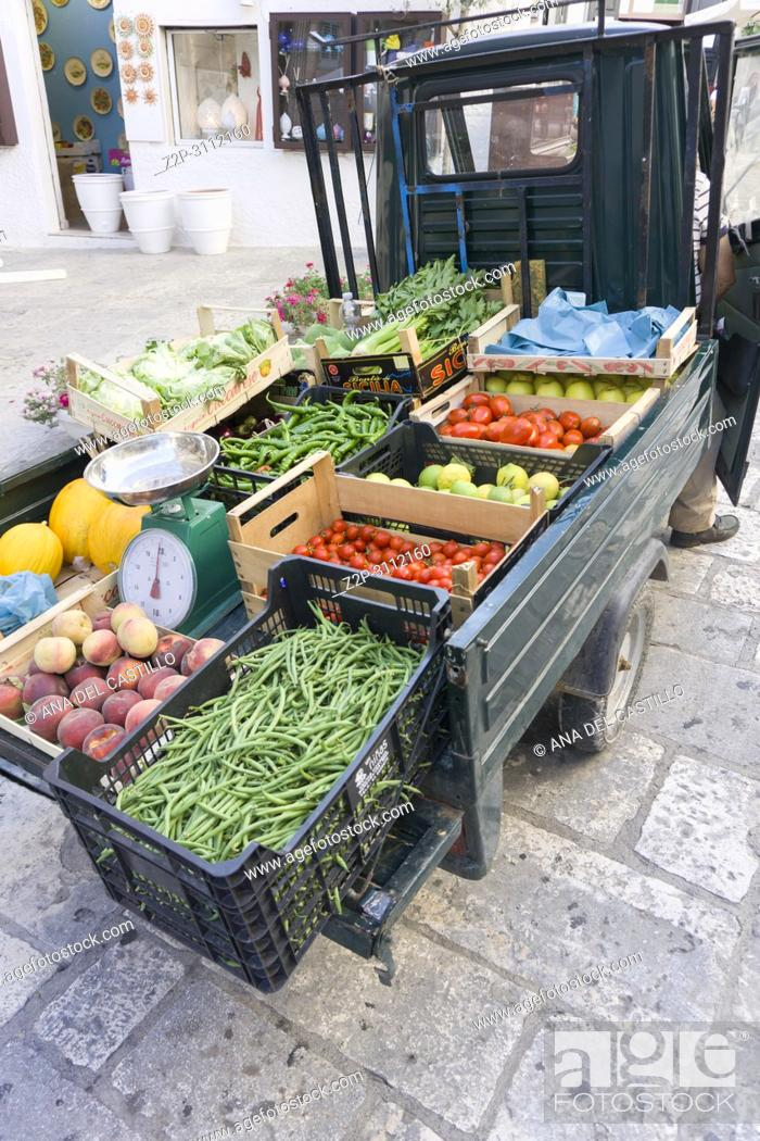 Imagen: Cityscape in Ostuni Brindisi Puglia Italy on July 13, 2018. Greengrocers in a three-wheeled motorcycle.