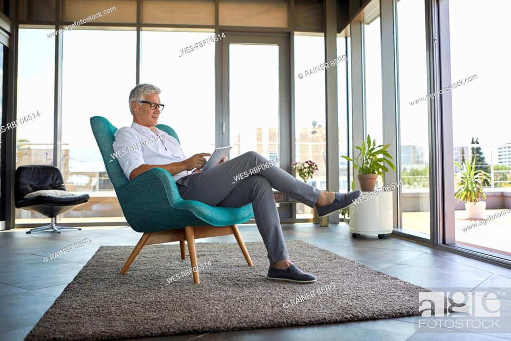 Stock Photo: Mature man sitting in armchair at home using tablet.