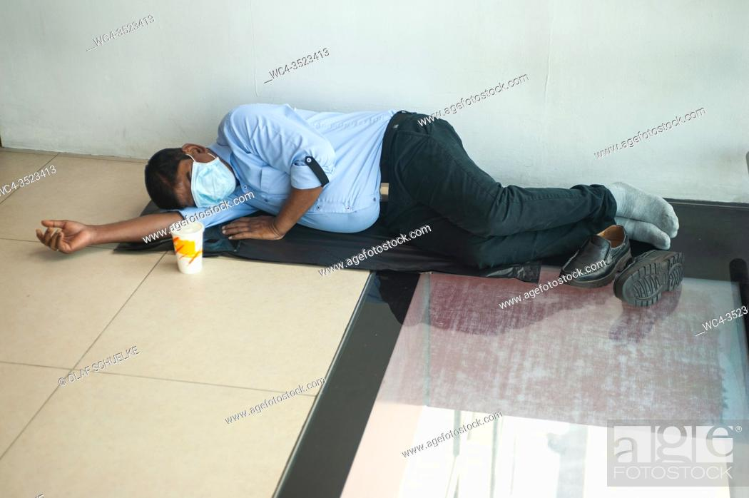 Stock Photo: Singapore, Republic of Singapore, Asia - A man wears a protective face mask to prevent an infection with the pandemic coronavirus as he sleeps on the floor of.